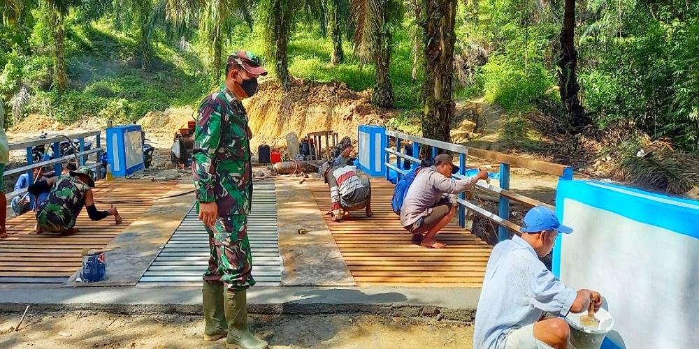 Warga Terus Ikut Bergotong Royong Mengecat Jembatan TMMD Kodim 0204/DS